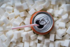 Soda can surrounded by sugar cubes