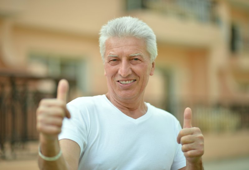 older man smiling thumbs up