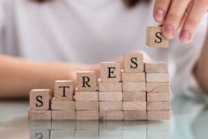 "person stacking blocks that spell out ""stress"""