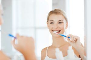 Woman brushing her teeth at her dentist.