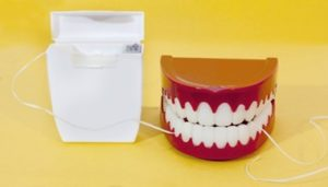 Dental floss container next to a set of toy teeth sitting against a yellow background