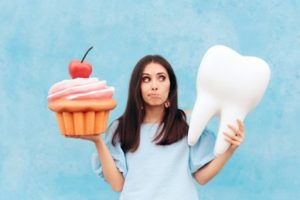 Woman holding a cupcake in one hand and a tooth in the other with a thoughtful look on her face.
